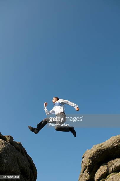 Businessman Leaps Between Big Boulders