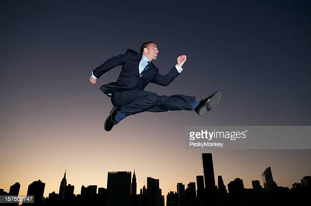 Businessman Leaps Over Sunset City Skyline Silhouette Dusk
