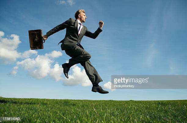 ビジネスマンが飛躍的に明るいグリーンの草地ブリーフケース