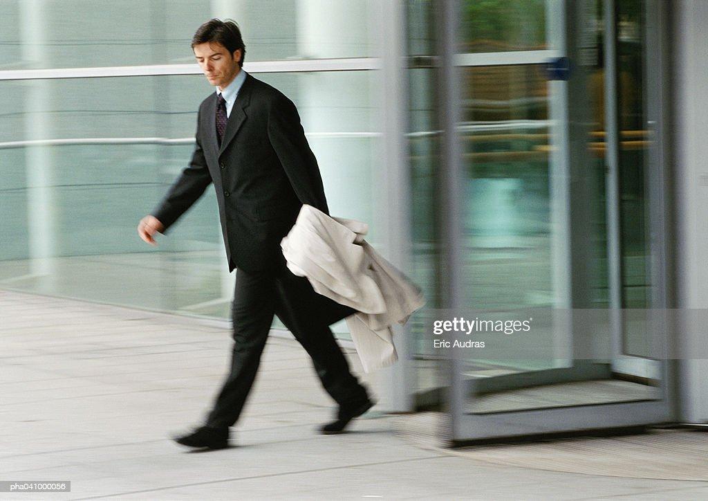 Businessman leaving building, holding overcoat, blurred : Stockfoto