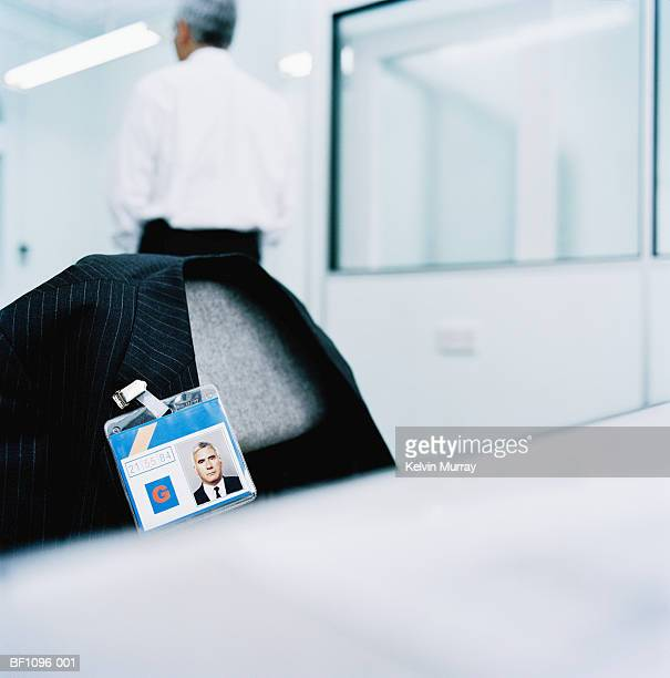Businessman leaving desk, focus on name badge on jacket left on chair