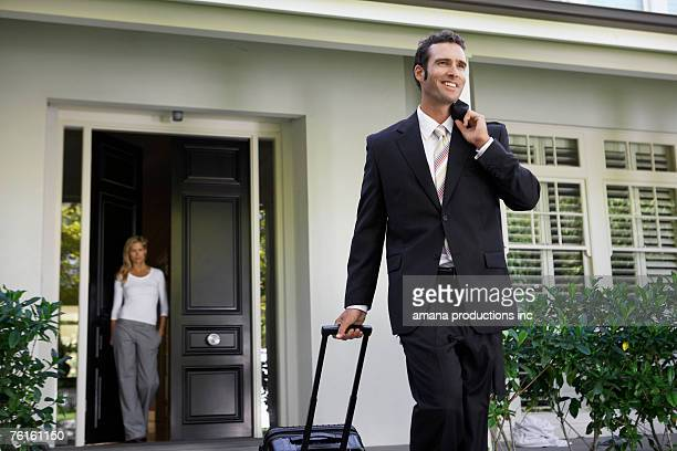Businessman leaving for business trip, wife at door
