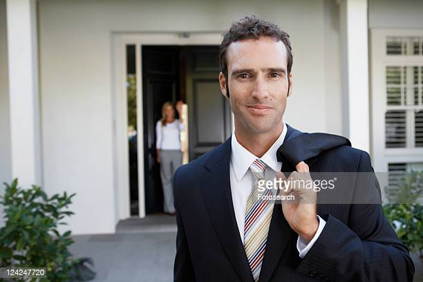Businessman leaving for work, wife at door