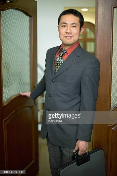 Businessman leaving home for work, portrait
