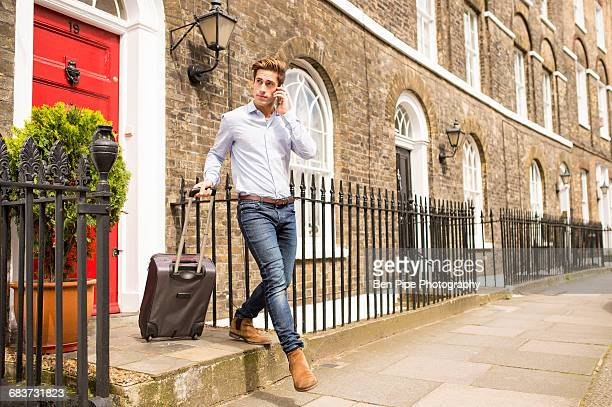 Businessman leaving house with wheeled suitcase, London, UK