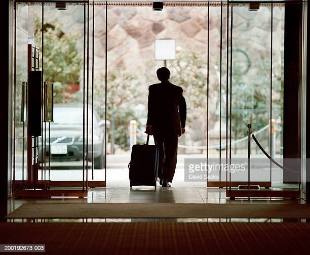Businessman leaving lobby with luggage, rear view