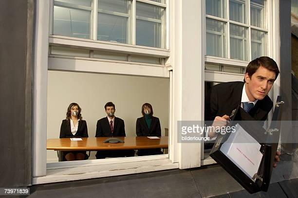 businessman leaving office building through window with confidential documents - gagged woman stock pictures, royalty-free photos & images