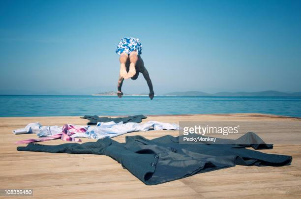 Businessman Leaving Suit Behind Diving into Water