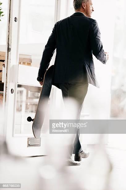 Businessman leaving through door, carrying skateboard