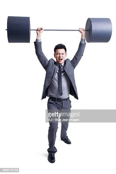 Businessman lifting barbell