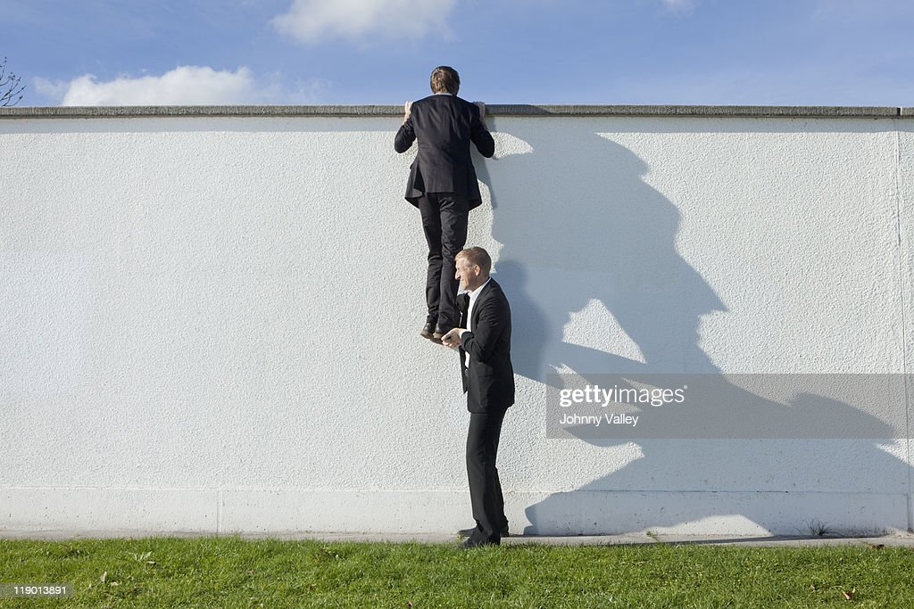 Businessman lifting colleague over wall : Stock Photo