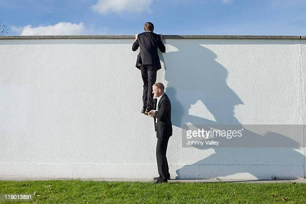 businessman lifting colleague over wall - ermutigung stock-fotos und bilder