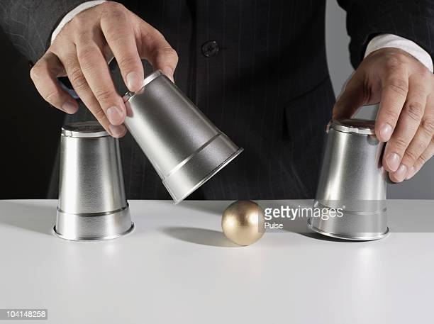 Businessman lifting cup of shell game