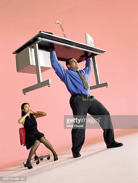 Businessman lifting desk, woman with shocked expression
