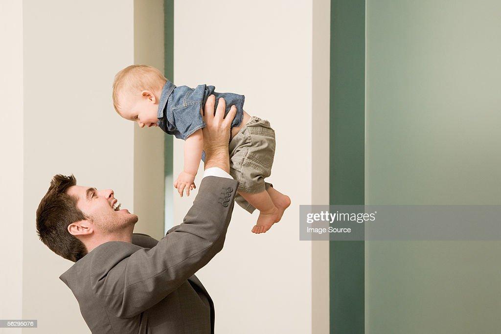 Businessman lifting his baby : Stock Photo