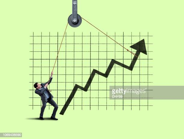 businessman lifting large arrow with rope and hoist - economy stock pictures, royalty-free photos & images