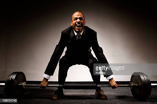 businessman lifting weights - struggle stock pictures, royalty-free photos & images