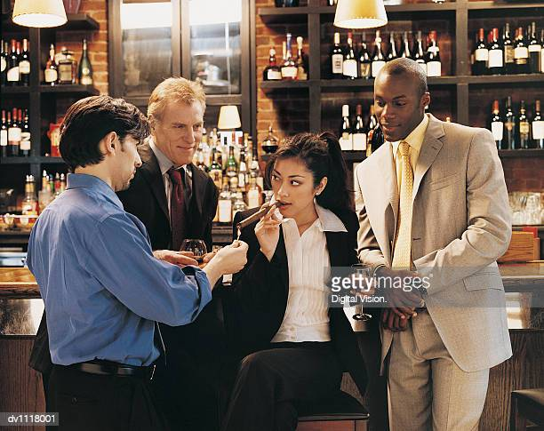 Businessman Lighting a Businesswoman's Cigar in a Bar Surrounded by Other Businessmen