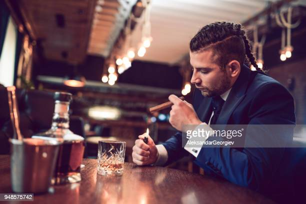 Businessman Lighting up a Cigar and Drinking Whisky in Restaurant