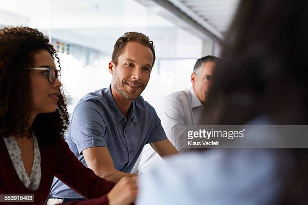 Businessman listening at coworker at meeting