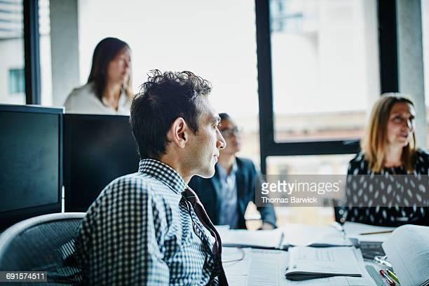 Businessman listening during informal team meeting