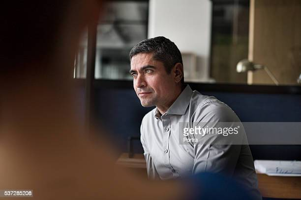 Businessman listening in meeting at office