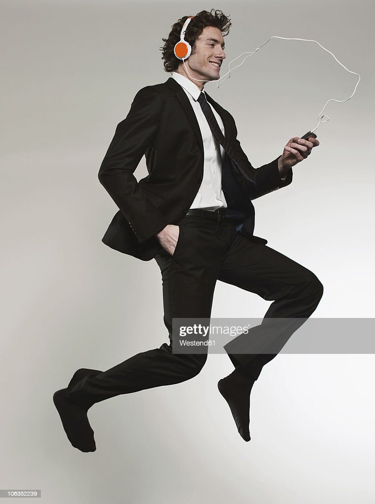 Businessman listening music and jumping, smiling : Stock Photo