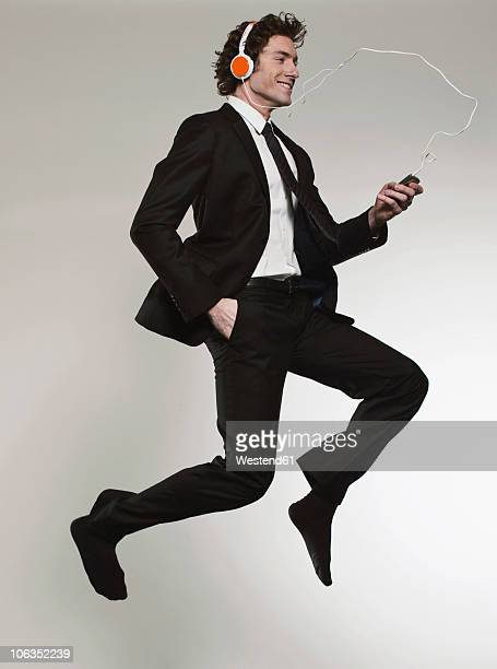 Businessman listening music and jumping, smiling