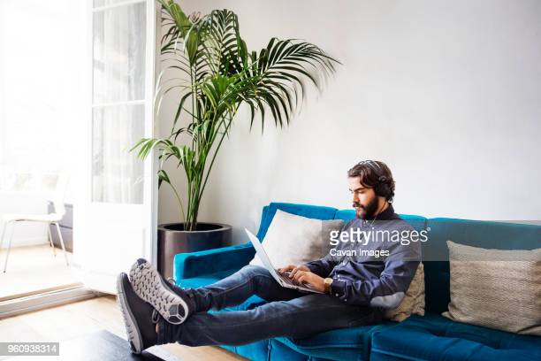 Businessman listening music while using laptop on sofa in office
