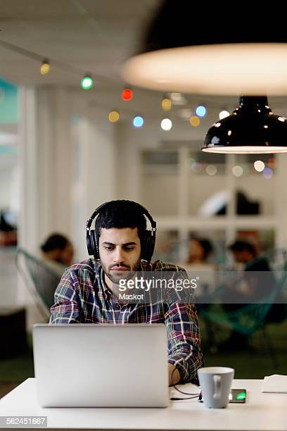 Businessman listening music while working late on laptop in creative office