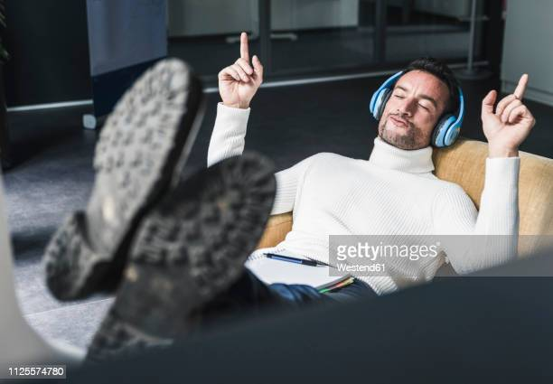 businessman listening relaxed music in his office - musical conductor stock pictures, royalty-free photos & images