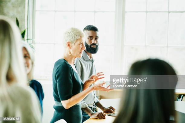 businessman listening to colleague present during project planning meeting in office - older women in short skirts stock pictures, royalty-free photos & images