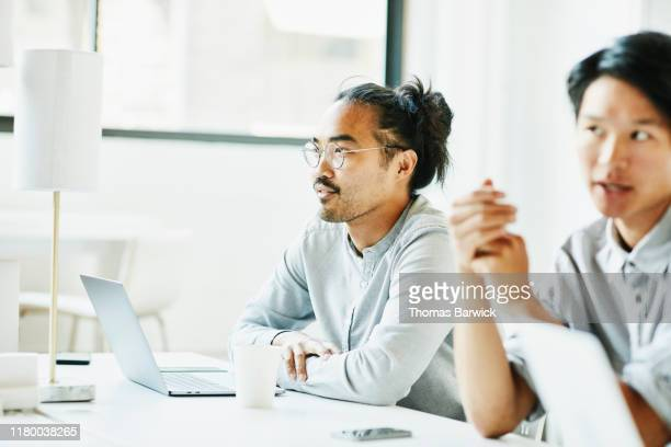 businessman listening to colleague while working in coworking office - pacific islander stock pictures, royalty-free photos & images