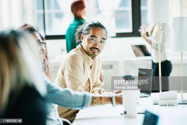 businessman listening to colleague while working in coworking office - creativity stock pictures, royalty-free photos & images