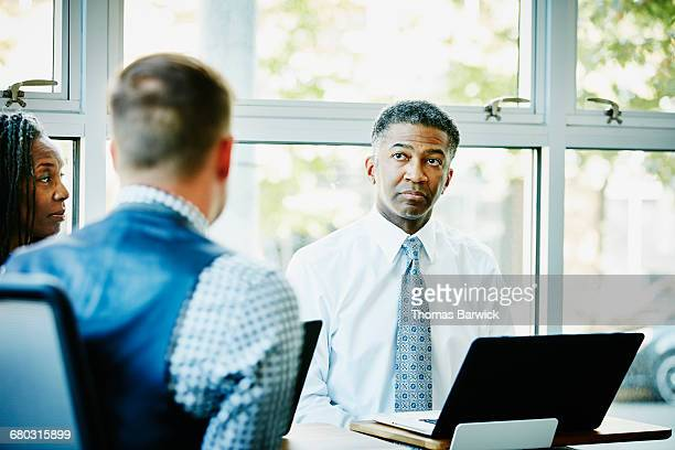 Businessman listening to coworker during meeting