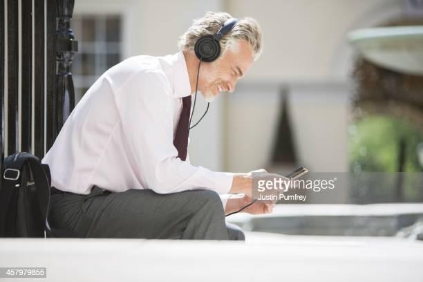 Businessman listening to headphones on city street