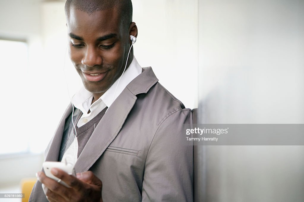 Businessman listening to MP3 player : Stock Photo