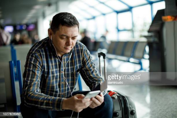 businessman listening to music on mobile phone while waiting a flight at airport - mp3 player stock pictures, royalty-free photos & images