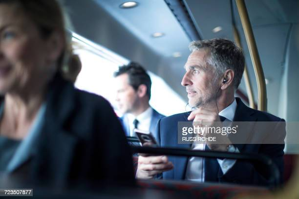 Businessman listening to smartphone earphones on double decker bus