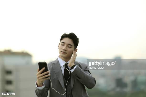 Businessman listening to smartphone earphones