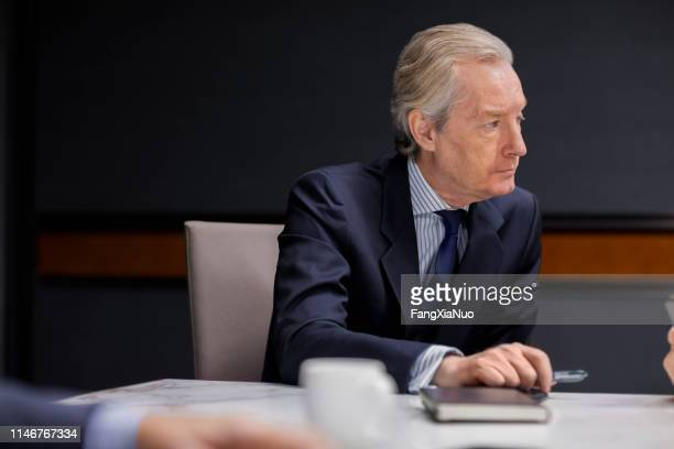 businessman listening to speaker in office meeting - shareholder stock pictures, royalty-free photos & images