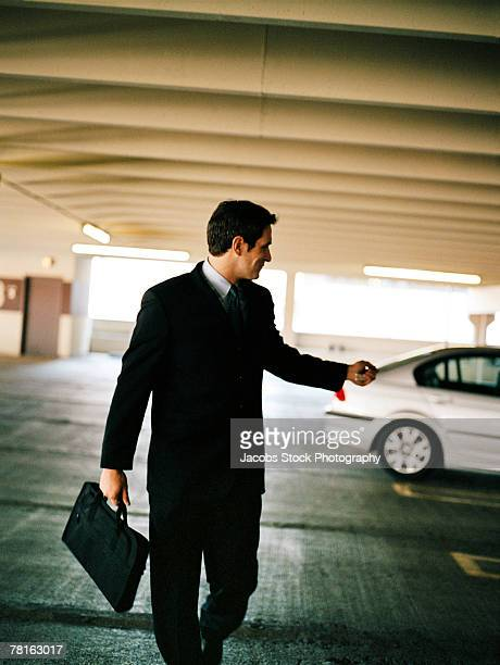 businessman locking car with remote key - car alarm stock photos and pictures