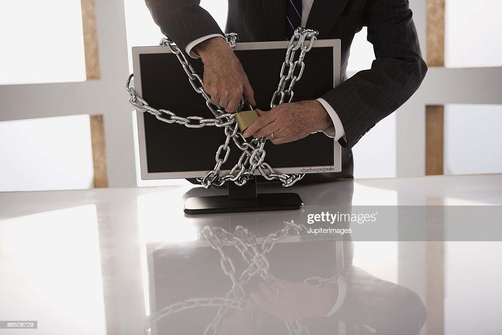 Businessman locking computer monitor : Stock Photo