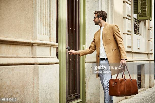 Businessman locking door at sidewalk in city