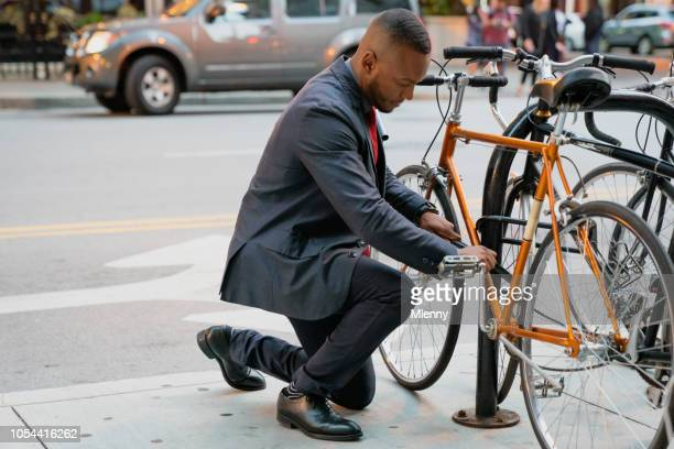 Businessman locking his bicycle in downtown Chicago