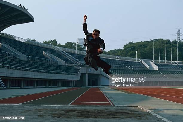 businessman long jumping in mid-air - 走り幅跳び ストックフォトと画像