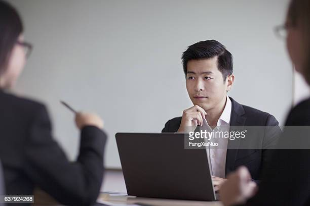 businessman looking across table in office meeting - asien stock-fotos und bilder