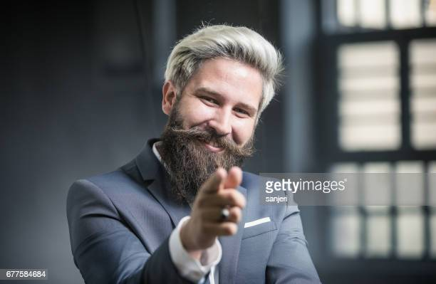 Businessman Looking and Pointing at Camera