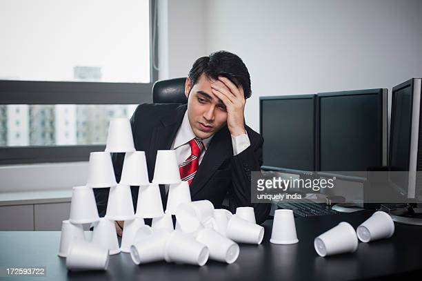 Businessman looking at a broken pyramid