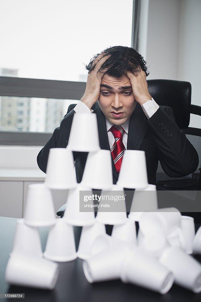 Businessman looking at a broken pyramid : Stock Photo